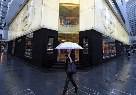 Mujer usa el móvil mientras va de compras por una zona exclusiva.